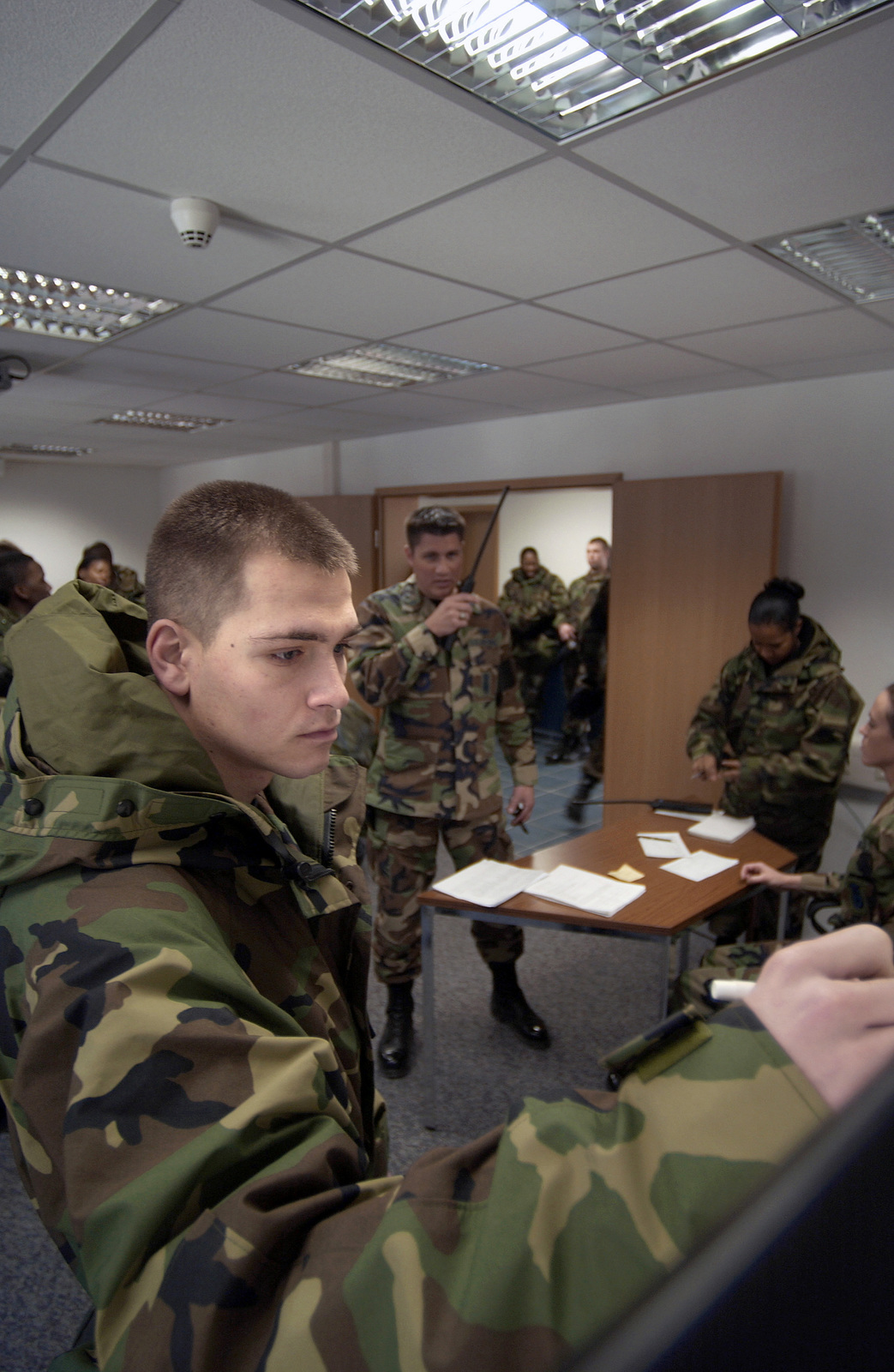 US Air Force (USAF) AIRMAN First Class (A1C) Chase Hoffman (foreground), 569th Security Forces Squadron (SFS), updates the operations board during a riot control training scenario at Vogelweh Air Station (AS), Kaiserslautern, Germany