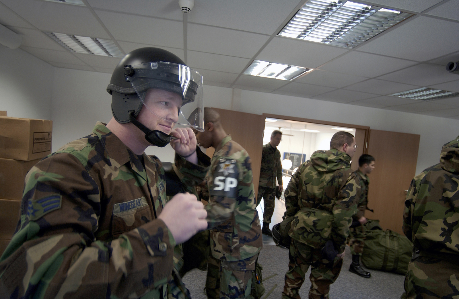 US Air Force (USAF) SENIOR AIRMAN (SRA) Erik Winegeart (foreground), 569th Security Forces Squadron (SFS), dons a riot control helmet before participating in training scenario at Vogelweh Air Station (AS), Kaiserslautern, Germany