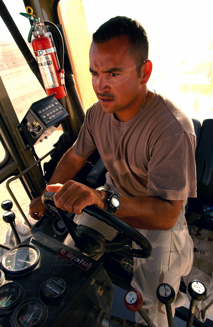 US Air Force (USAF) STAFF Sergeant (SSGT) Juan Marquis-Abundis, Heavy Equipment Operator, 823rd Red Horse Squadron (RHS), pictured in the cab of a self-propelled vibratory roller during a taxiway and support ramp construction project at a forward deployed location during Operation ENDURING FREEDOM