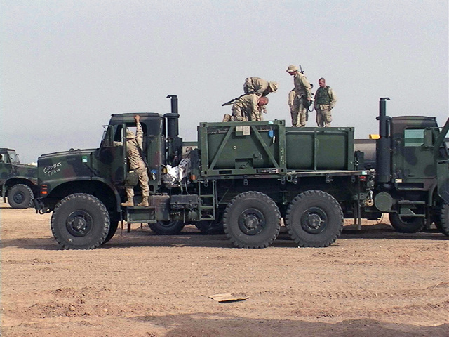 US Marine Corps (USMC) Marine Refuelers from Motor T (Transport) Platoon (PLT), Headquarters & Service (H&S) Company (CO), 2nd Tank Battalion (TK BN), Marine Corps Base (MCB) Camp Lejune, North Carolina (NC), prepare their Medium Tactical Vehicle Replacement (MTVR) vehicles to run fuel at a bore sighting exercise at the Udari Range complex in Kuwait during Operation ENDURING FREEDOM