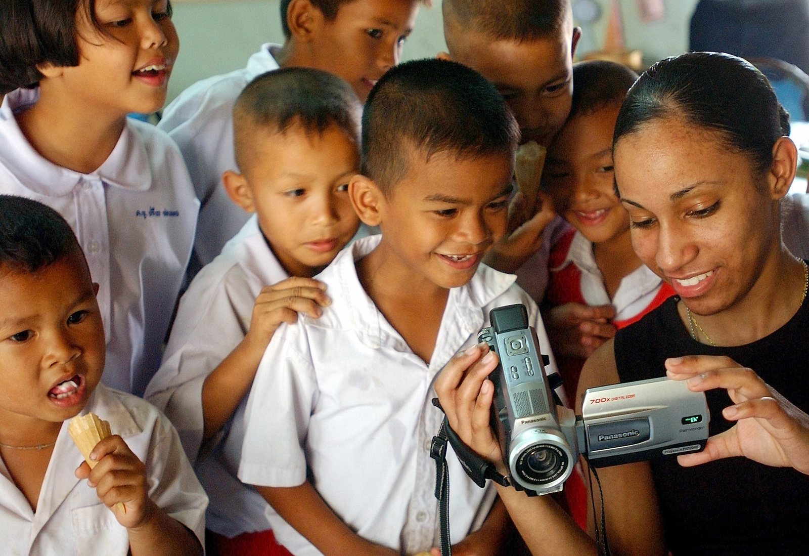 US Marine Corps (USMC) Private First Class (PFC) Vivian E. Lantigua, assigned to the Marine Air Logistics Squadron, shares her digital pictures with School Children during a community outreach event conducted during Exercise COPE TIGER 2003. Exercise participants raised money to purchased supplies that were donated to the school during the community outreach event. Cope Tiger is an annual multinational exercise in the Asia-Pacific region that promotes closer relations and enables air force units in the region to sharpen air combat skill and practice interoperability with US Forces