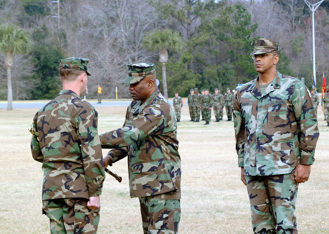 While Sergeant Major (SGM) Alexander McBride, right, looks on, the Headquarters and Headquarters Squadron (HHS), SGM Orlando E. Maxwell surrenders his sward to his Commanding Officer, Lieutenant Colonel (LCOL) Micheal W. McErlean, the reading of orders, on the parade deck of Marine Corps Air Station (MCAS) Beaufort, South Carolina