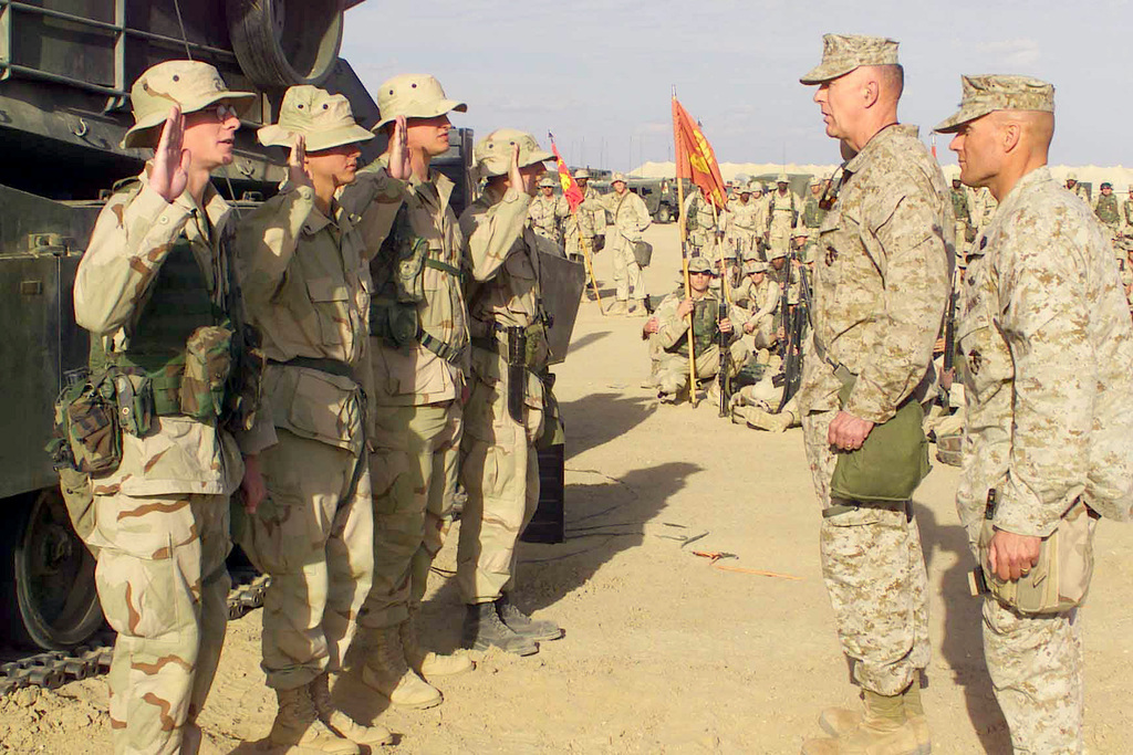 Four US Marine Corps (USMC) Marines of Regimental Combat Team 5, 1ST Marine Division out of Camp Pendleton, California, stand before USMC Lieutenant General (LGEN) James T. Conway, Commanding General, 1ST Marine Expeditionary Force (MEF), Camp Pendleton, California (CA), and the regiment as they re-enlist prior to being promoted meritoriously at Camp Coyote in Northern Kuwait during Operation ENDURING FREEDOM. Standing (left to right) are: USMC Lance Corporal (LCPL) William S. Green, 2nd 5th Marines, 1ST Marine Division, Camp Pendleton, CA; USMC LCPL Aaron K. Chapman, 3rd 5th Marines, 1ST Marine Division, Camp Pendleton, CA; USMC LCPL Joseph W. Sharpe, 1ST...