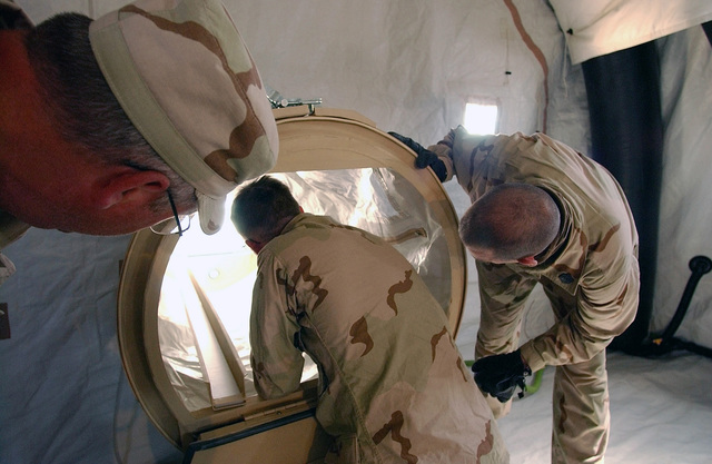 US Navy (USN) Hospital Corpsman Second Class (HM2) Johnathan Bradford (center) and USN HM2 Thomas Miller (right), both assigned to the 2nd Force Services Support Group (FSSG), work together to assemble a patient airlock for a Chemical Biological Protective Shelter (CBPS), while US Department of Defense (DOD) Equipment SPECIALIST, Mr. Dan Breitenstein, supervises, during a training exercise conducted at Camp Coyote, Kuwait, during Operation ENDURING FREEDOM. The CBPS is a highly mobile chemically protected shelter system designed for emergency medical use in forward battle areas