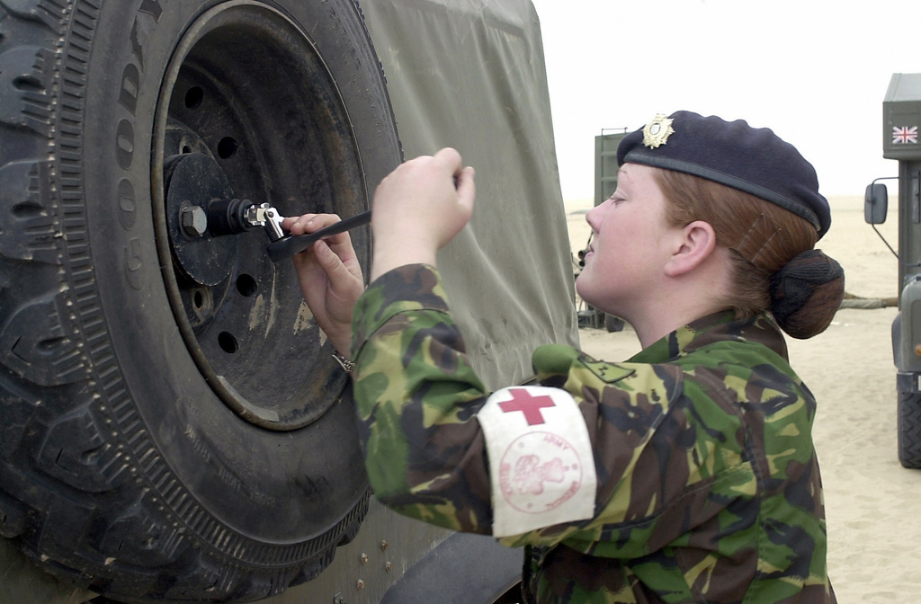 British Army Private (PTE) Barbara Davis loosens the lug nuts on a field medical Land Rover at Camp Fox, Kuwait, to change a flat tire. PTE Davis is a driver in A (11) Squadron 4 General Support Medical Regiment deployed in support of Operation ENDURING FREEDOM