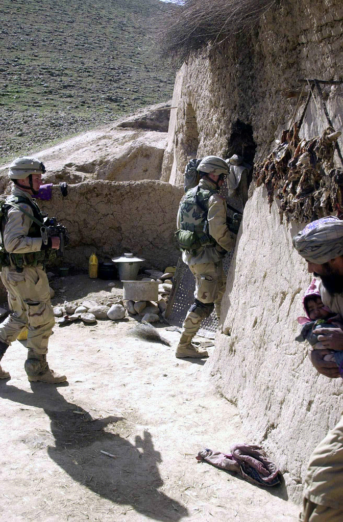 """Soldiers with """"B"""" Company, 2nd Battalion, 504th Parachute Infantry Regiment (PIR), from Fort Bragg, North Carolina, armed with 5.56mm M4 Carbine rifles, search a house for Taliban weapons caches in the Baghran Valley during Operation Viper, in support of Operation ENDURING FREEDOM"""