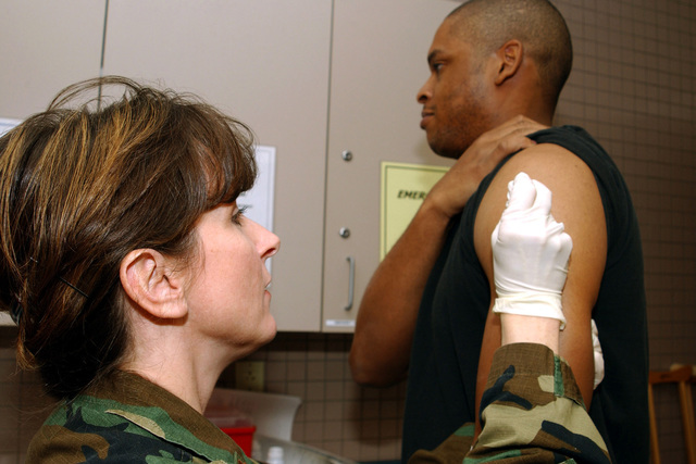 US Air Force (USAF) Major (MAJ) Michelle Galarneau, a Nurse assigned to the 169th Medical Squadron, gives a Smallpox vaccination to SENIOR AIRMAN (SRA) Calvin Adger, 169th Maintenance Squadron, as USAF Airmen assigned to the 169th Fighter Wing (FW), South Carolina (SC), Air National Guard (ANG), process for deployment at McEntire Air National Guard Station (ANGS), Columbia, SC
