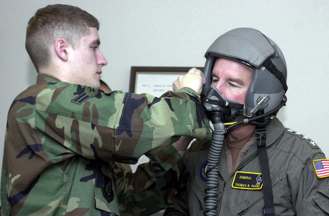 "US Air Force (USAF) AIRMAN First Class (A1C) Andrew Coyner (left), Life Support Specialists, 12th Aircraft Maintenance Unit (AMU) at Elmendorf AFB, fits US Navy (USN) Admiral (ADM) Thomas Fargo, Commander, US Pacific Command, with a flight helmet and oxygen mask prior to his flight at Elmendorf Air Force Base (AFB), Alaska (AK). Admiral Fargo flew with the 12th Fighter Squadron (FS), otherwise known as ""The Dirty Dozen,"" during his visit to Elmendorf"