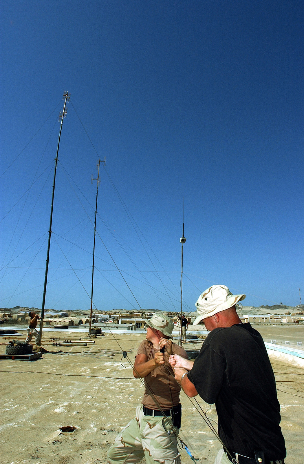 US Air Force (USAF) SENIOR AIRMAN (SRA) John Goll, left and STAFF Sergeant (SSGT) Mitchell Mason, wideband satellite journeyman assigned to the 321st Expeditionary Communications Squadron (ECS), raise the second of five Very High Frequency (VHF) 60-foot masts at a forward-deployed location, in support of Operation ENDURING FREEDOM