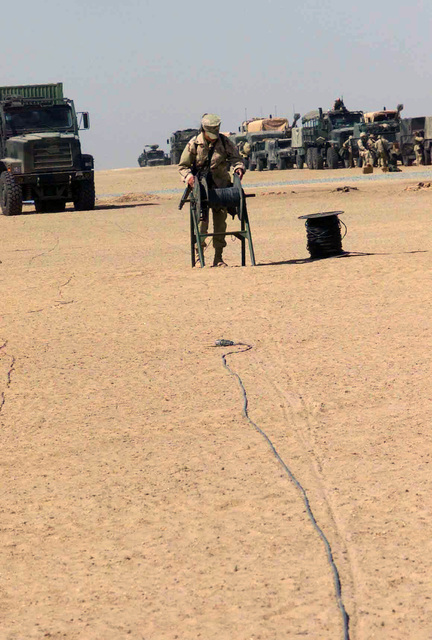US Marine Corps (USMC) Lance Corporal (LCPL) Yazzie, 1ST Marine Division (MAR DIV), Communications Company (COMM CO), Wire Platoon (PLT), reels up some cable at Camp Matilda during Operation ENDURING FREEDOM