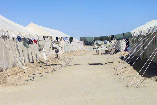 US Marine Corps (USMC) Marines rig up a clothesline between tents to dry their clothes faster in the desert wind and heat at Camp Matilda during Operation ENDURING FREEDOM