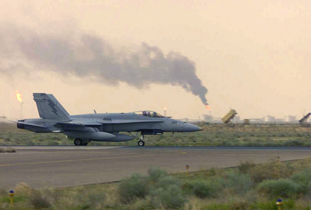 A US Marine Corps (USMC) F/A-18D Hornet Taxis past smoke plumes and patriot missile systems at Al Jaber Air Base, Kuwait, in support of Operation ENDURING FREEDOM