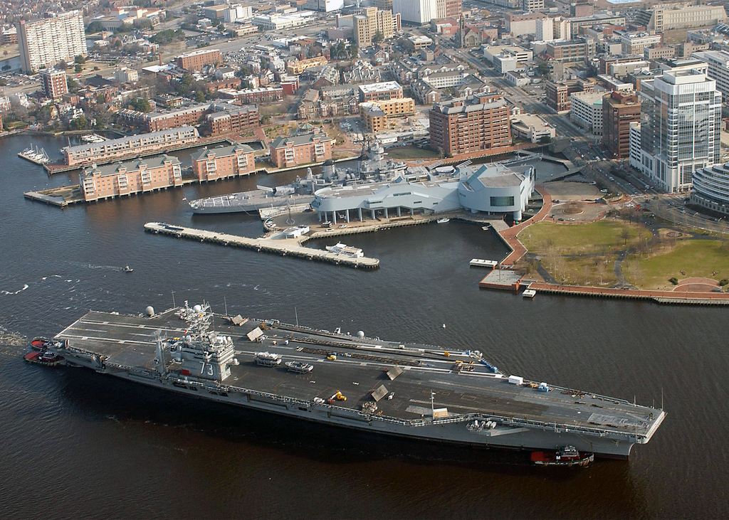 The US Navy (USN) Nimitz class Aircraft Carrier USS GEORGE WASHINGTON (CVN 73) passes by the USN Iowa class Battle Ship USS WISCONSIN (BB 64), near downtown Norfolk during her transit down the Elizabeth River from Norfolk Naval Station to Norfolk Naval Shipyard in Portsmouth, Virginia (VA)
