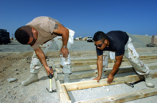 US Air Force (USAF) SENIOR AIRMAN (SRA) Eduardo Barajas, left and SRA Hector Caro, a heating, ventilation and air conditioning journeymen assigned to the 321st Expeditionary Civil Engineering Squadron (CES), build floor frames for temper tents at a forward-deployed location, in support of Operation ENDURING FREEDOM