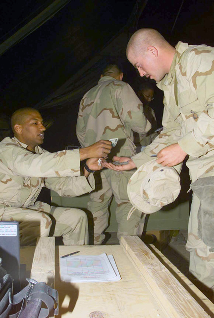 US Marine Corps (USMC) Lance Corporal (LCPL) Roy Clay (left), Pay Non-Commissioned Officer (NOC) from the WEST Team, assigned to 3/4 Headquarters/Company, issues cash payment to Sergeant (SGT) Jason Kavanugh, at Camp Coyote, Kuwait, during Operation ENDURING FREEDOM