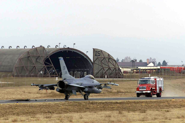 An emergency response vehicle approaches a US Air Force (USAF) F-16CJ Fighting Falcon aircraft, assigned to the 23rd Fighter Squadron (FS), as the aircraft comes to a stop after engaging the barrier arresting system cable on the North Atlantic Treaty Organization (NATO) Parallel taxiway, during a certification test, being conducted by the 52nd Civil Engineer Squadron (CES), 52nd Fighter Wing (FW), at Spangdahlem Air Base (AB), Germany. (Duplicate image, see also DFSD0500934 or search 030228F0718S014)