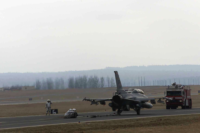 US Air Force (USAF) Firefighters assigned to the 52nd Civil Engineer Squadron (CES), 52nd Fighter Wing (FW), conduct a certification test of the aircraft arresting gear barrier cable on the North Atlantic Treaty Organization (NATO), Parallel taxiway, using a 23rd Fighter Squadron (FS) F-16CJ Fighting Falcon aircraft, at Spangdahlem Air Base (AB), Germany
