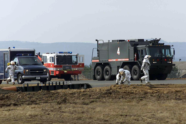US Air Force (USAF) Firefighters assigned to the 52nd Civil Engineer Squadron (CES), 52nd Fighter Wing (FW), respond in force using an emergency response van (left), a P-24 Structural Pumper Fire Truck (center), and a P-23 Heavy Crash Truck, during a barrier arresting system cable, certification test, being conducted on the North Atlantic Treaty Organization (NATO) Parallel taxiway at Spangdahlem Air Base (AB), Germany