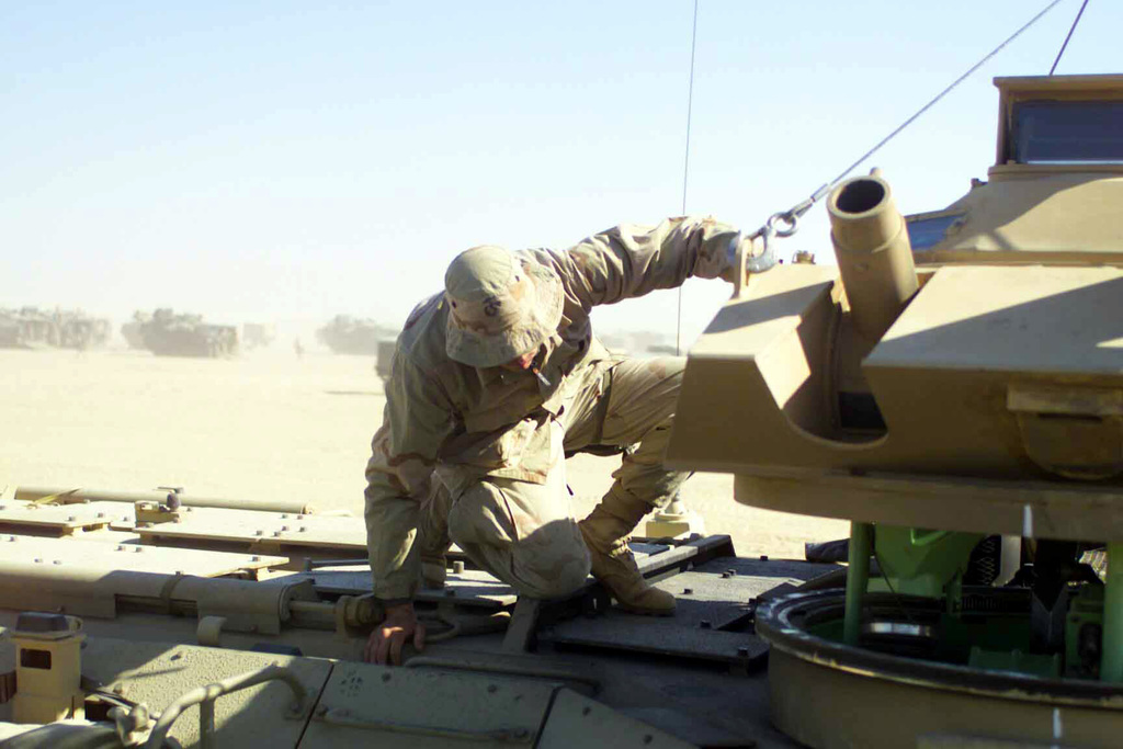 US Marine Corps (USMC) Lance Corporal (LCPL) Kevin Dieu, a Marine with Delta Company, 3rd Tracks, lowers the turret to an Amphibious Assault Vehicle (AAV) into position at Camp Coyote, Kuwait, during Operation ENDURING FREEDOM