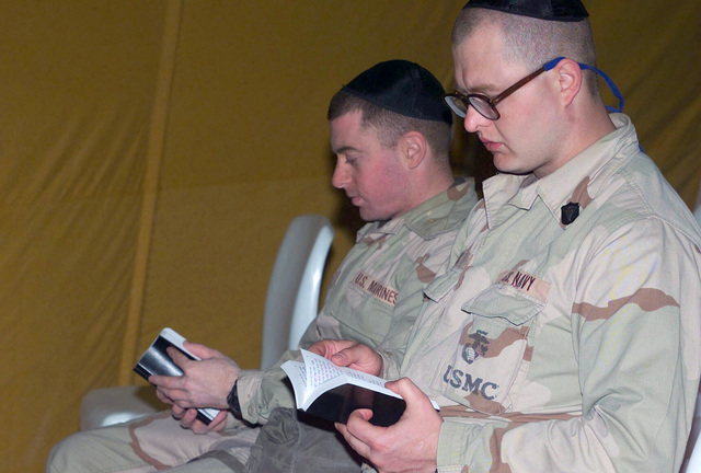 US Marine Corps (USMC) Second Lieutenant (2LT) Ethan Astor (left), 1ST Battalion (BN), 4th Marines (MAR) and US Navy (USN) Hospital Corpsman Second Class (HM2) Mark Nix, 4th Amphibious Assault Battalion (AAB), Alfa Company, attend a Jewish service in the Chaplain's tent at Camp Matilda, Kuwait during Operation ENDURING FREEDOM