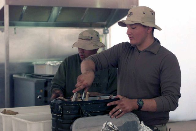 US Marine Corps (USMC) Food Service Specialists Lance Corporal (LCPL) Isaac Preston (left) and LCPL Rodolfo Guarec, remove fresh cooked chicken, from an insulated food container, as they prepare to serve evening chow at Camp Matilda, Kuwait, during Operation ENDURING FREEDOM
