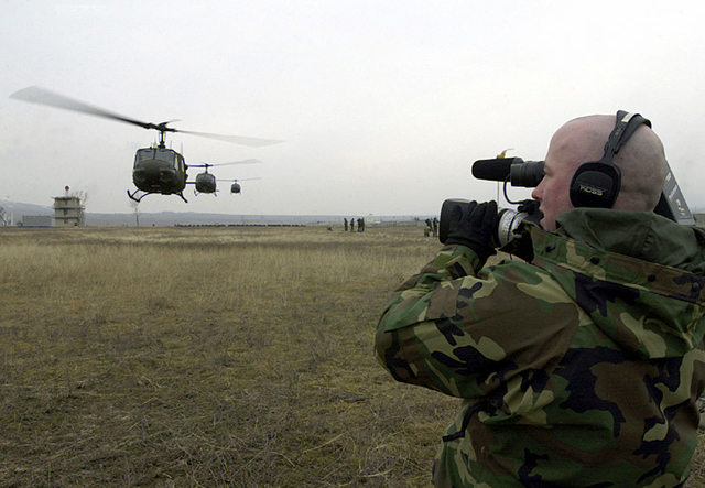 A US Air Force (USAF) two man documentation team led by Technical Sergeant (TSGT) Ed Prince, from the 886th Communications Squadron (CS), Sembach Annex, Germany documents the arrival of several UH-1 Iroquois helicopters, flying in support of the Georgia Train and Equip Program (GTEP)