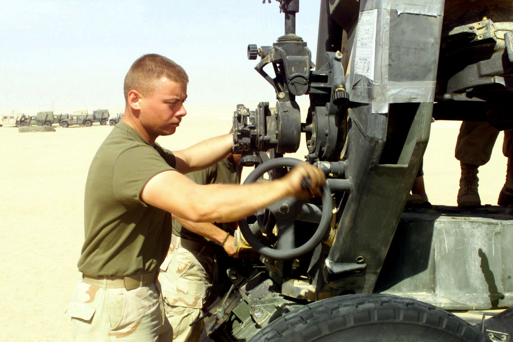 At Camp Coyote, Kuwait, checking his M198 155mm howitzer for proper operation, US Marine Corps (USMC) Sergeant (SGT) Matthew Davis, Lima Battery, 3rd Battalion, 11th Marine Regiment (3/11), cranks the hand wheel to traverse the piece during Operation ENDURING FREEDOM