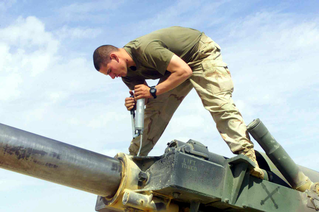 US Marine Corps (USMC) Private First Class (PFC) Brad Menhorn, with Lima Battery, 3rd Battalion, 11th Marines, lubes grease points on a Howitzer artillery piece at Camp Coyote, Kuwait, during Operation ENDURING FREEDOM