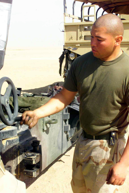 US Marine Corps (USMC) Sergeant (SGT) Alejandro Alaniz, with Lima Battery, 3rd Battalion, 11 Marines, traverses a Howitzer artillery piece left, during a periodic cleaning, at Camp Coyote, Kuwait, in support of Operation ENDURING FREEDOM