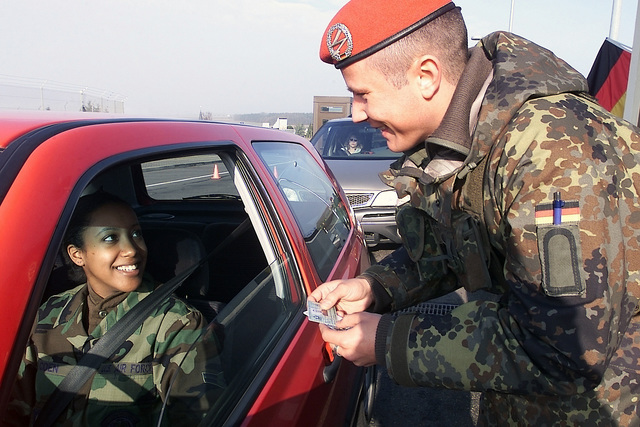 German Bundeswehr Soldier STAFF Sergeant (SSGT) Marc Schumacher, checks the Identification of US Air Force (USAF) AIRMAN First Class (A1C) Daneirys Coen, of the 52nd Communications Squadron (CS), Spangdahlem Air Base (AB), Germany (DEU)