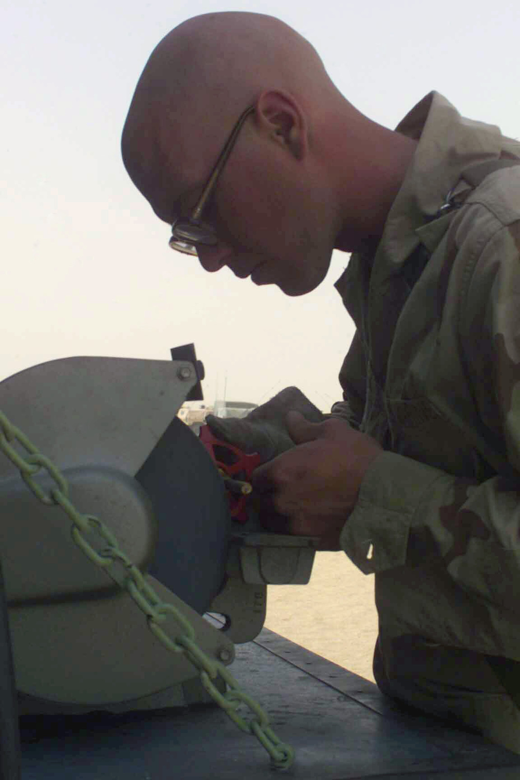 US Marine Corps (USMC) Lance Corporal (LCPL) Adam Wilson, Headquarters Company, Maintenance Platoon, 1ST Tanks, fixes a twist knob for pipes in the showers at Camp Coyote, Kuwait, during Operation ENDURING FREEDOM