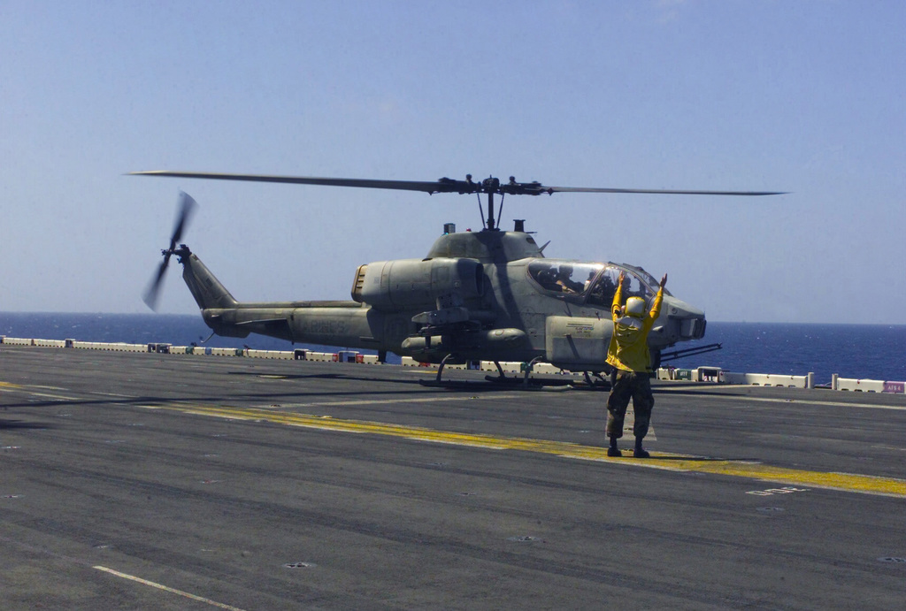 A US Navy (USN) Aircraft Handling Officer signals to a US Marine Corps (USMC) AH-1W Super Cobra helicopter from Marine Medium Helicopter Squadron 263 (HMM-263), 24th Marine Expeditionary Unit (MEU), Special Operations Capable (SOC), as it lifts off from the flight deck aboard the US Navy (USN) WASP CLASS: Amphibious Assault Ship, USS NASSAU (LAH 4), during Operation ENDURING FREEDOM