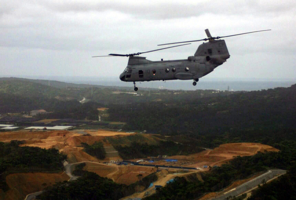A US Marine Corps (USMC) CH-46 Sea Knight Helicopter assigned to Marine Medium Helicopter Squadron Two Six Five (HMM-265) flies over a green mountainous region, during a simulated troop insertion exercise, at Camp Butler, Okinawa, Japan. (Substandard image)