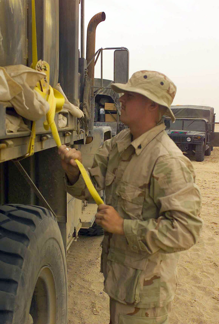 US Marine Corps (USMC) Corporal (CPL) Bryon Hightower, 1ST Light Armored Reconnaissance Battalion (LARB), 1ST Marine Division, Motor Transport, tightens a cargo strap on his 5-ton truck at Camp Grizzly, Kuwait, during Operation ENDURING FREEDOM