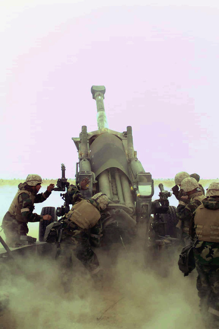 US Marine Corps (USMC) Marines assigned to gun two, L/Battery, 1ST Marine Division, fire their M198 155mm Howitzer towards Iraq, at Camp Matilda, Kuwait, in support of Operation IRAQI FREEDOM