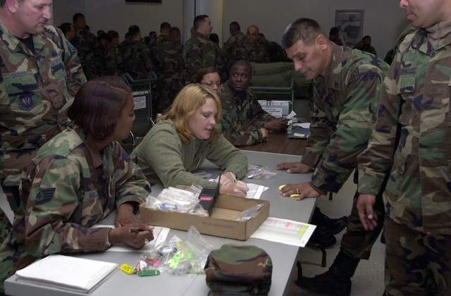 US Air Force (USAF) STAFF Sergeant (SSGT) Alyssa Barclay, left and Jennifer James, from the 100th Service Squadron (SS), Royal Air Force (RAF) Base Mildenhall, England, distribute billeting keys to STAFF Sergeant (SSGT) Jose Olmeda, First Sergeant (1SGT) US Army (USA), Charlie Company, 192nd Medical Support Unit, an Army National Guard (ANG) unit from Puerto Rico