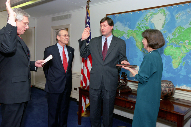 The Honorable Donald H. Rumsfeld (left), U.S. Secretary of Defense, observes and Mrs. Margaret Cambone (right) holds the Bible as the Honorable Raymond F. Dubois, Jr. (left), Deputy Under Secretary of Defense for Installations and Environment, administers the oath of office to Dr. Stephen Cambone (second from right), incoming Under Secretary of Defense for Intelligence, during the swearing-in ceremony for Dr. Cambone on March 11, 2003.  OSD Package No. A07D-00516 (DOD PHOTO by Robert D. Ward) (Released)