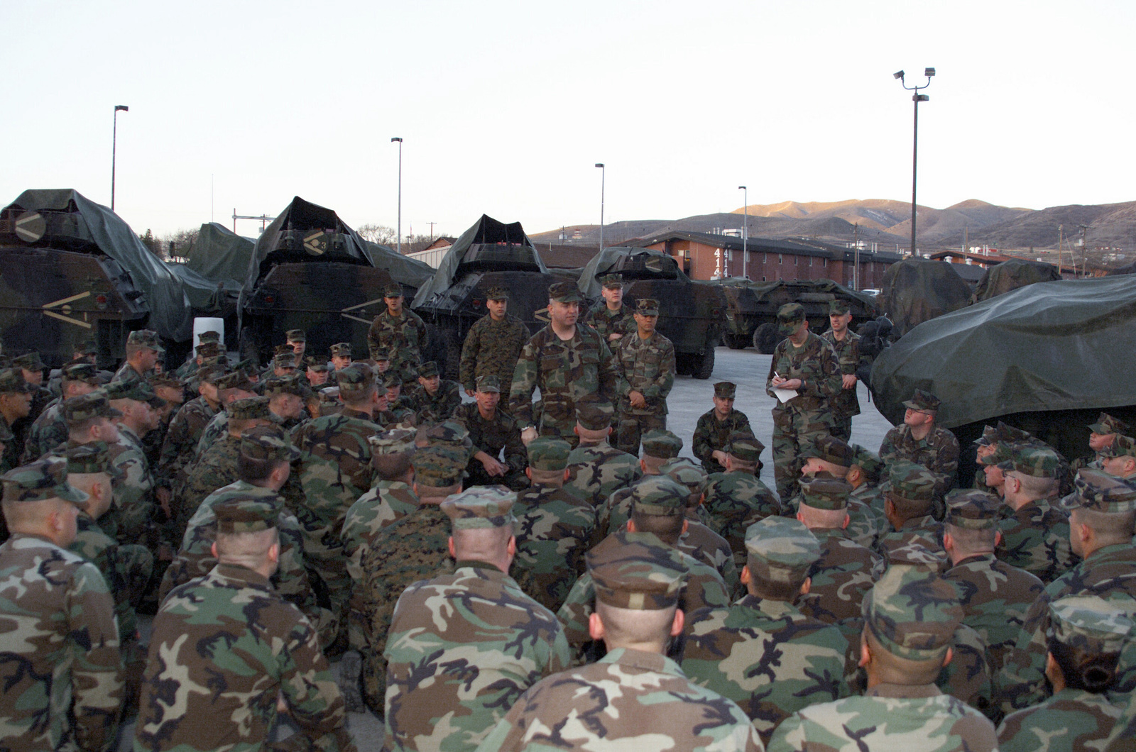 US Marine Corps (USMC) personnel from Charlie Company, 4th Light Armored Reconnaissance (LAR) Battalion, 4th Marine Division, form a school circle around First Sergeant (1SGT) Dikenson, in support of OPERATION IRAQI FREEDOM