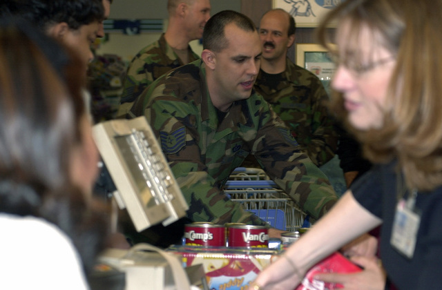 "The US Air Force (USAF), 86th Airlift WingΘs (AW), Non-Commissioned Officer (NCO) of the Year for""2002"", Technical Sergeant (TSGT) Mark Smurda, unloads one of many shopping carts after his 5-minute shopping spree sponsored by the Defense Commissary Agency, at Ramstein Air Base Germany. This year was the first time that the Wing Annual Award winners were presented with a shopping spree as a prize"