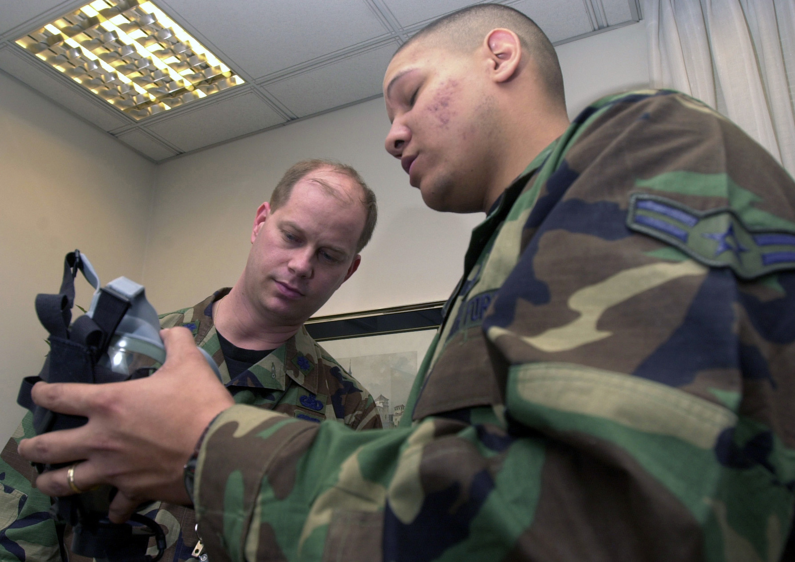 US Air Force (USAF) Lieutenant Colonel (LCOL) John Foden, left, Logistics Readiness Center (LRC) CHIEF, for the 16th Air Expeditionary Task Force (AETF), receives guidance on how to wear his gas mask from SENIOR AIRMAN (SRA) Drew Hall, a Readiness Trainer, with the 31st Civil Engineer Squadron (CES)