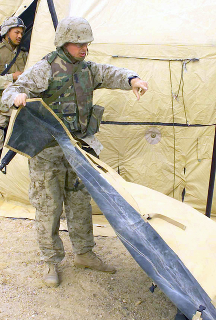US Marine Corps (USMC) Corporal (CPL) Brian Singer, lays down a panel while building a section of the medical Sick Tent for the 7th Marines, Regiment S-4, in support of Operation ENDURING FREEDOM, at Camp Ripper, Kuwait