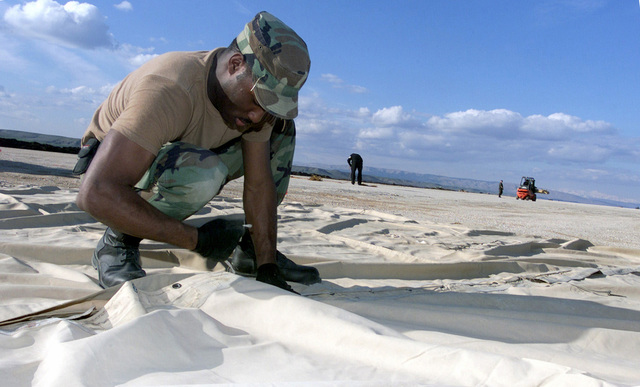 US Air Force (USAF) AIRMAN First Class (A1C) Stevon Douglas, a plumber from the 52nd Air Expeditionary Wing (AEW), tethers a tent at a forward-deployed location, in support of the War on Terror