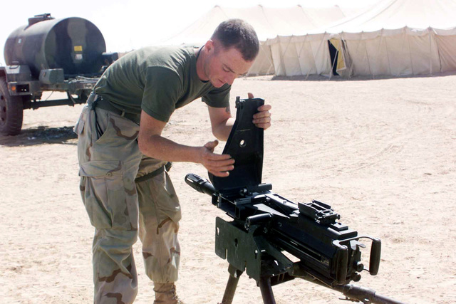 US Marine (USMC) Corporal (CPL) Patrick H. Weston, Combat Support Service (CSS), 1ST Battalion, 11th Marines (1/11), practices weapon familiarization by disassembling and reassembling an MK 19 Mod 3 40mm grenade machine gun system, at Living Support Area 1 (LSA 1), during Operation ENDURING FREEDOM