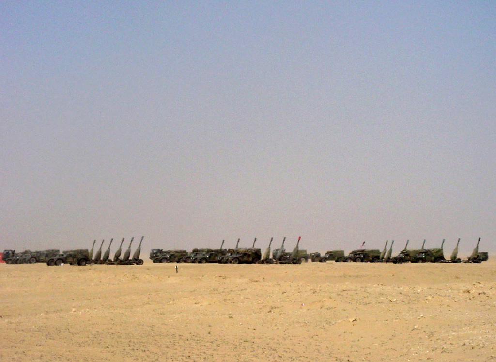 US Army (USA) High-Mobility Multipurpose Wheeled Vehicles (HMMWV) and M198 155mm Towed Howitzers parked in the Division Artillerys big guns motor pool, at Camp New Jersey, Kuwait, during Operation ENDURING FREEDOM. (SUBSTANDARD)