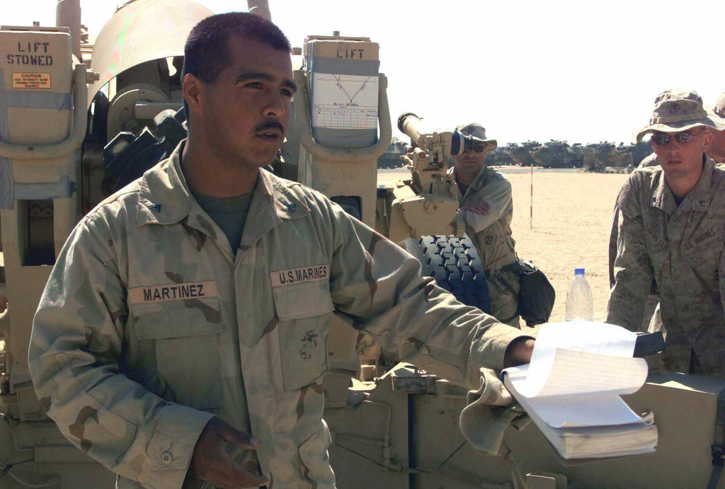 US Marine Corps (USMC) Corporal (CPL) Joe Martinez (foreground) Assistant CHIEF Howitzer Operator from India/Battery, 11th Marines, gives a safety briefing to the Marines of Weapons/Company, 7th Marines, on the M198 155mm towed Howitzer, at Camp Ripper, Kuwait, during Operation ENDURING FREEDOM