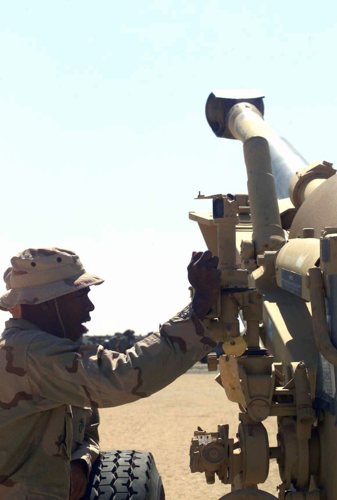 US Marine Corps (USMC) Corporal (CPL) Mack Mahlon, assigned to Weapons/Company, 1ST Battalion, 7th Marines, makes adjustments on the M138 elbow telescope, while conducting training on the M198 155mm towed Howitzer, at Camp Ripper, Kuwait, during Operation ENDURING FREEDOM