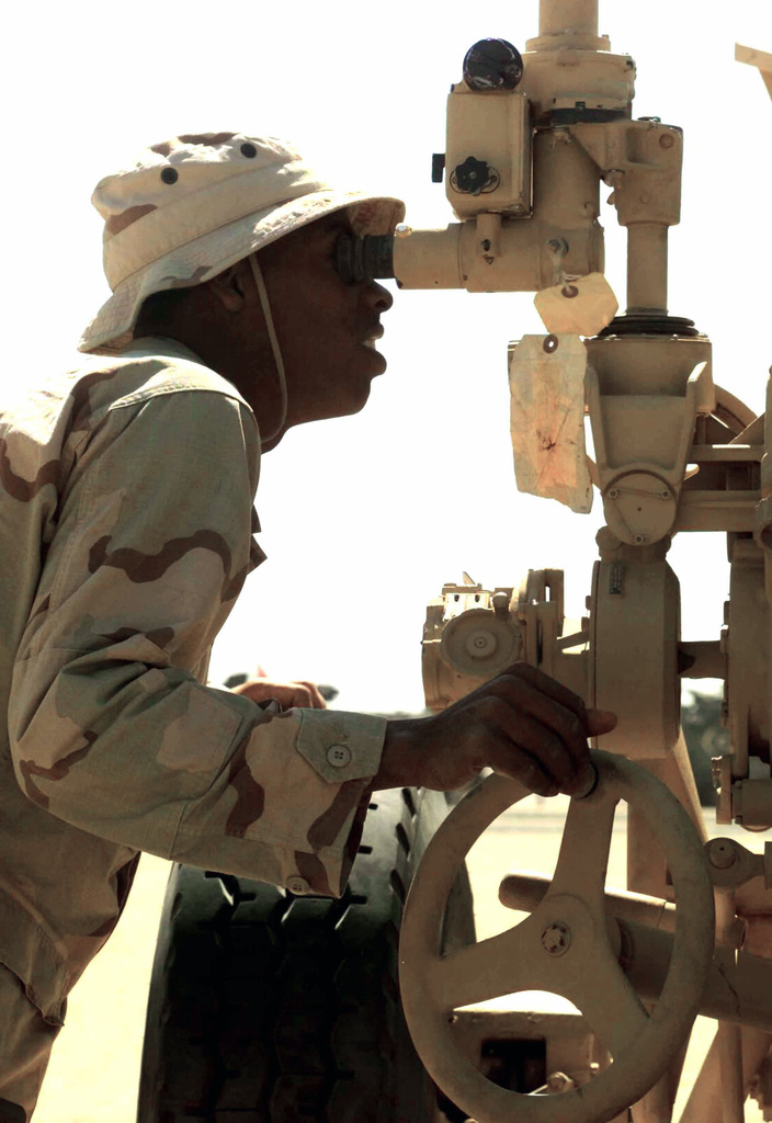 US Marine Corps (USMC) Corporal (CPL) Mack Mahlon, assigned to Weapons/Company, 1ST Battalion, 7th Marines, makes site adjustments using the M138 elbow telescope, while conducting training on the M198 155mm towed Howitzer, at Camp Ripper, Kuwait, during Operation ENDURING FREEDOM