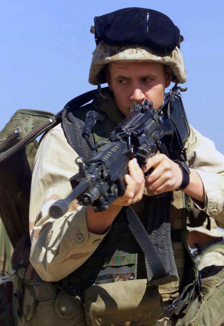 US Marine Corps (USMC) Lance Corporal (LCPL) Jeremiah Rice, Rifleman, 2nd Platoon, 1ST Battalion, 7th Marines (1/7), Charlie Company, Twentynine Palms, California (CA), practices entering and clearing rooms with his FNMI 7.62 mm M249 Squad Automatic Weapon (SAW), at Camp Ripper, Kuwait, during Operation ENDURING FREEDOM