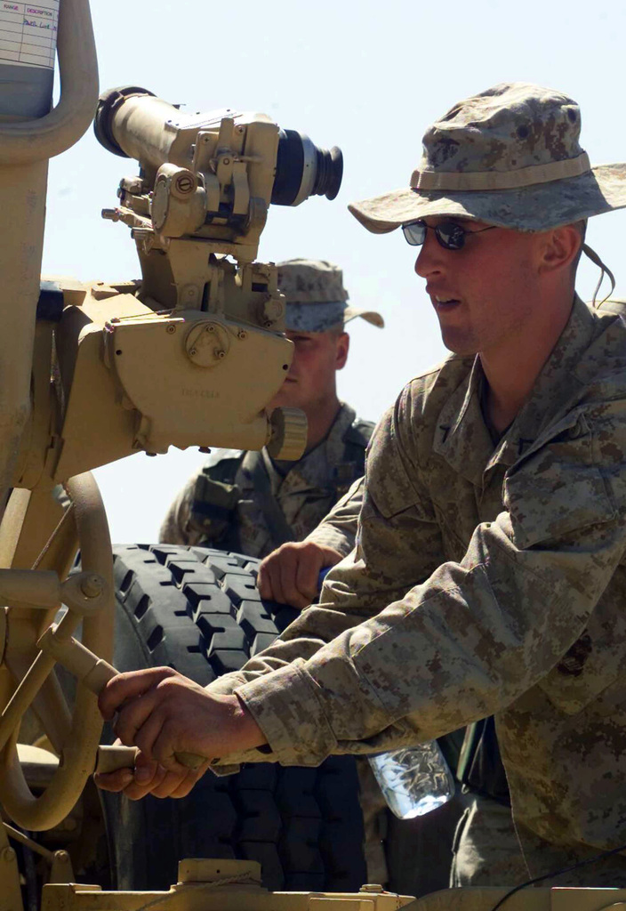 US Marine Corps (USMC) Private First Class (PFC) Michael Paulmeyer, assigned to Weapons/Company, 1ST Battalion, 7th Marines, makes site adjustments on a M198 155mm towed Howitzer, at Camp Ripper, Kuwait, during Operation ENDURING FREEDOM