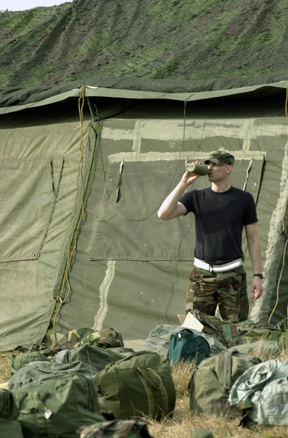 US Air Force (USAF) AIRMAN First Class (A1C) David Lewandowski, Electronic, Computers, and Switching Systems Technician, 603rd Air Control Squadron (ACS), quenches his thirst from his canteen after setting up tents in the field during the Survive to Operate (STO) course conducted at Aviano Air Base (AB), Italy